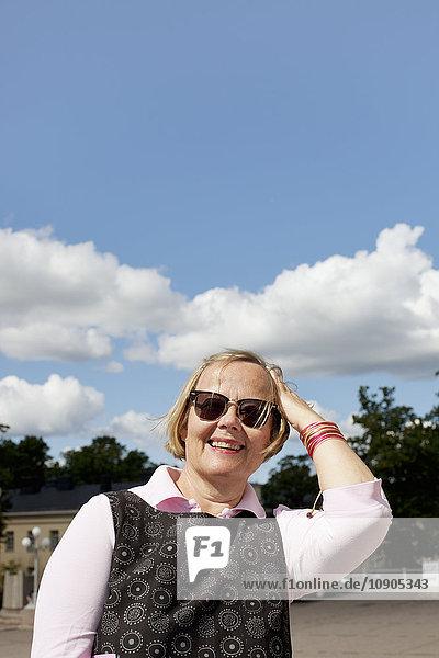 Finnland  Lächelnde Seniorin an einem sonnigen Tag