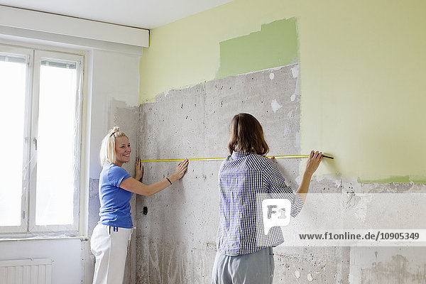 Finnland  Junge Frauen messen Wand für die Renovierung