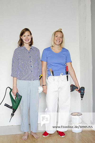 Finnland  Junge Frauen  die an der Wand stehen und Bohrer halten