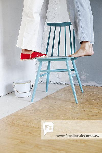 Finnland  Frauen  die auf einem Stuhl stehen  mit Lackdose
