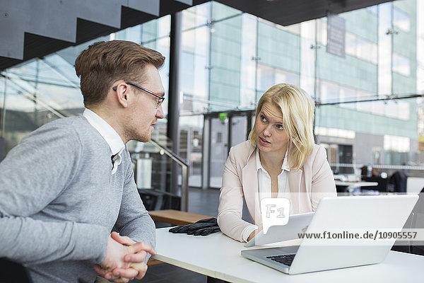 Finnland  Kollegen am Schreibtisch sitzen und reden