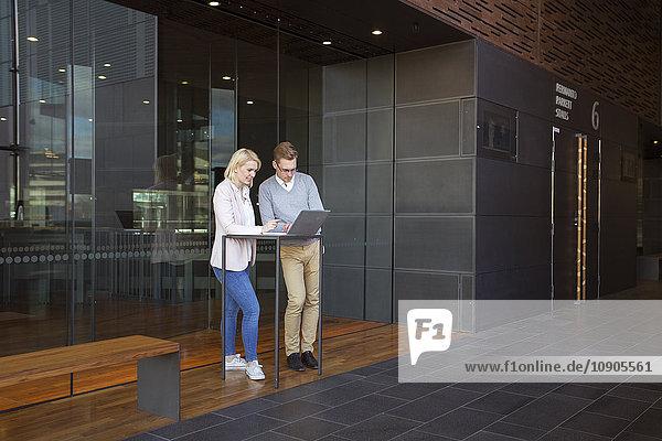 Finnland  Kollegen mit Laptop in der Lobby