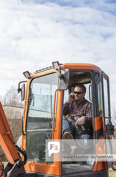 Finnland  Pohjanmaa  Pietarsaari  Mann sitzt in der Planierraupe und telefoniert