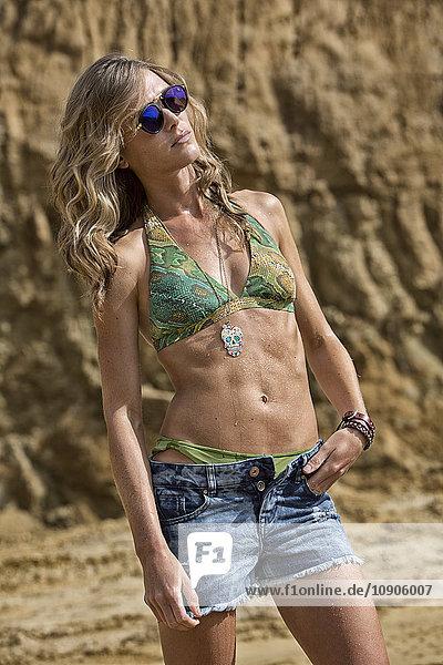 Blond woman wearing bikini and denim shorts