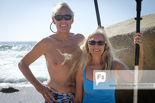 Portrait of happy senior couple holding paddles by the sea