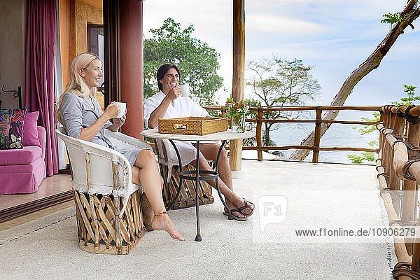 Happy couple sitting on terrace drinking coffee