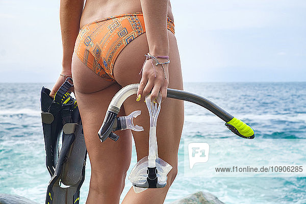 Young woman with diving equipment by the sea