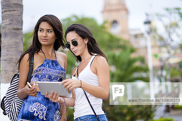 Mexico  Puerto Vallarta  two young women with tablet