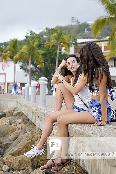 Mexico  Puerto Vallarta  two young women sitting at the Malecon in downtown