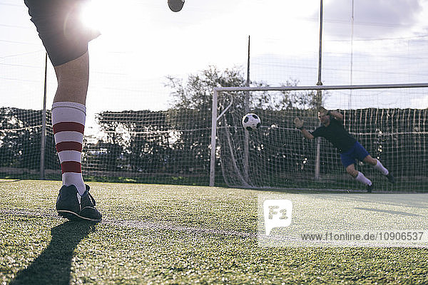 Legs of a footnball player kicking a ball in front of a goal with a goalkeeper