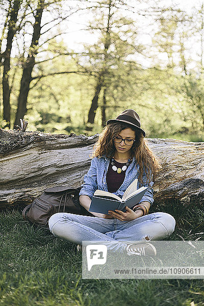 Woman sitting on a meadow reading a book
