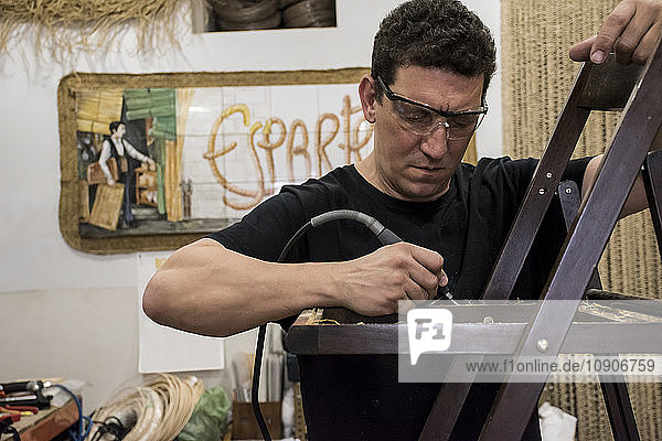 Ropemaking  Espartero with safety glasses cleaning a chair with an electric sander