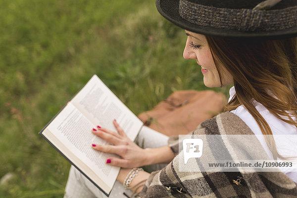 Junge Frau sitzt auf einer Wiese und liest ein Buch.
