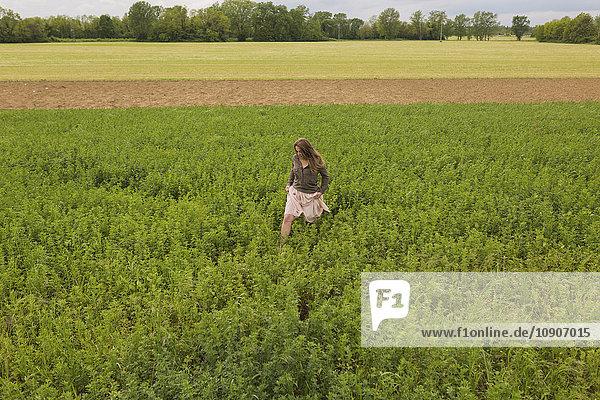 Eine Frau  die auf einem Feld läuft.