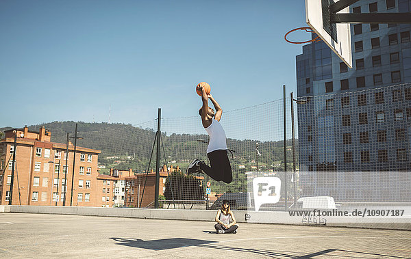 Junger Mann zielt auf Basketballkorb