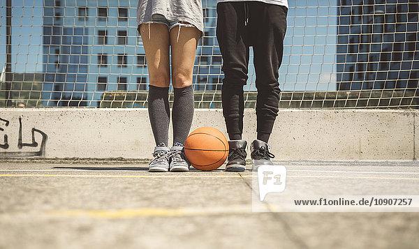 Junger Mann und Frau stehen auf dem Basketballfeld mit zwischen den Füßen.