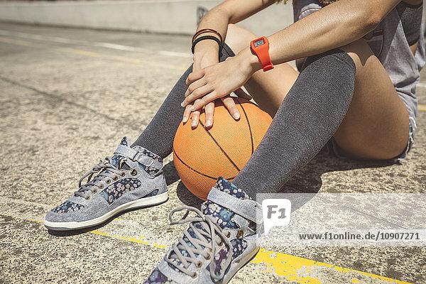 Junge Frau sitzt auf dem Boden des Baketballplatzes mit Ball zwischen den Beinen