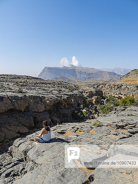 Oman  Jebel Shams  woman sitting on viewing point