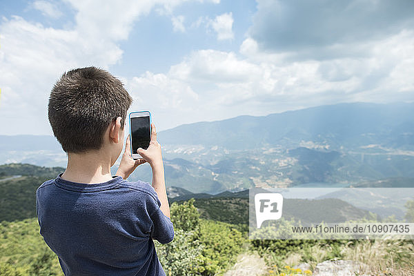 Greece  Central Macedonia  boy taking smartphone picture in the mountains