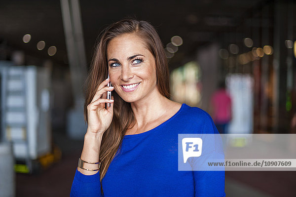Lächelnde brünette Frau am Handy
