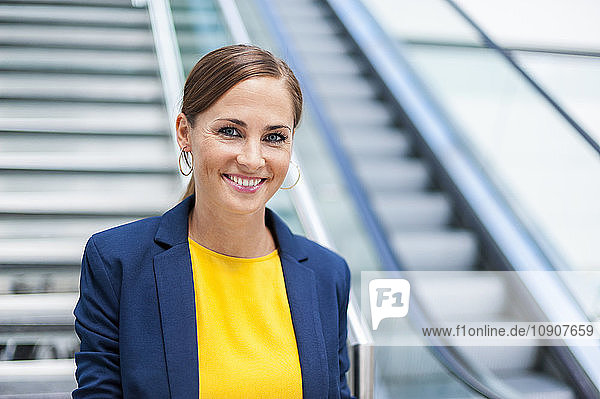 Portrait of smiling woman in front of escalator