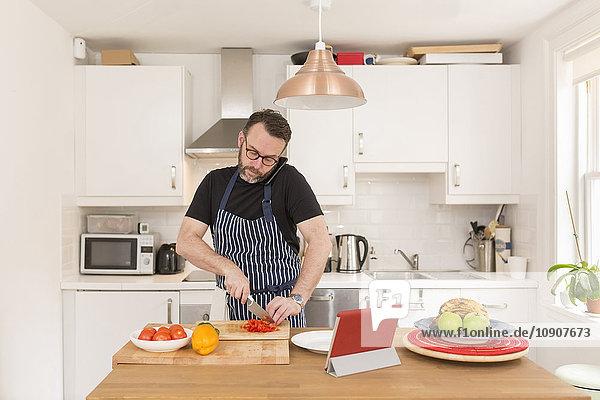 Telefonieren mit dem Smartphone während der Zubereitung von Gemüse in der Küche
