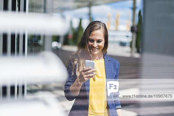 Smiling woman outdoors looking at cell phone