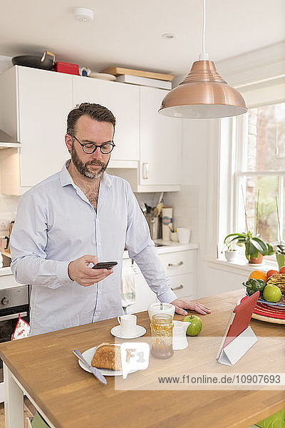 Man standing in his kitchen in the morning looking at his smartphone