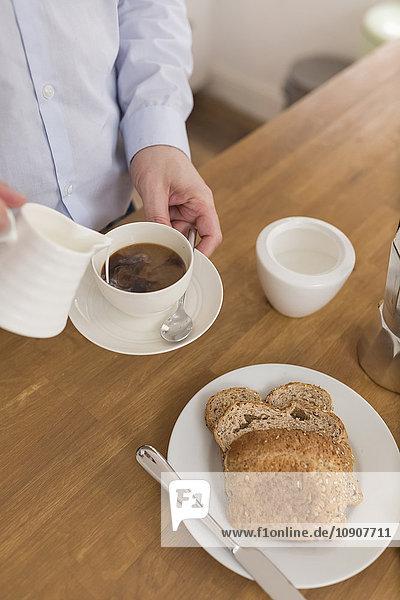 Mann gießt Milch in Kaffeetasse am Frühstückstisch  Teilansicht