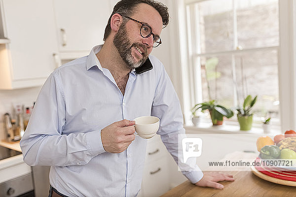 Man standing in the kitchen with cup telephoning with smartphone