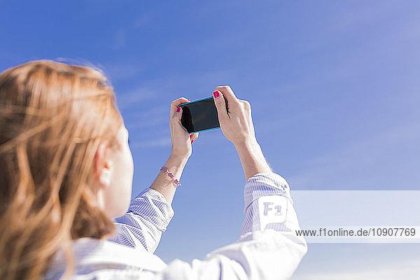 Italy  Lignano Sabbiadoro  woman with smartphone  selfie