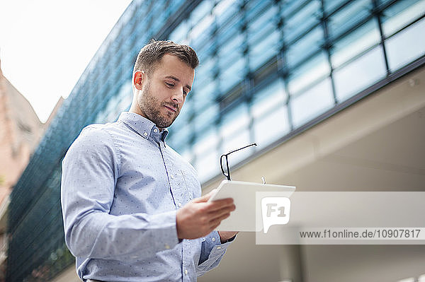Young man looking at tablet outdoors