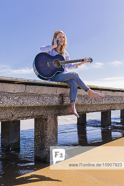 Woman with smartphone and guitar sitting on jetty