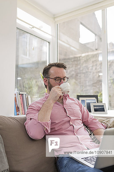 Mature man on couch drinking coffee and using laptop