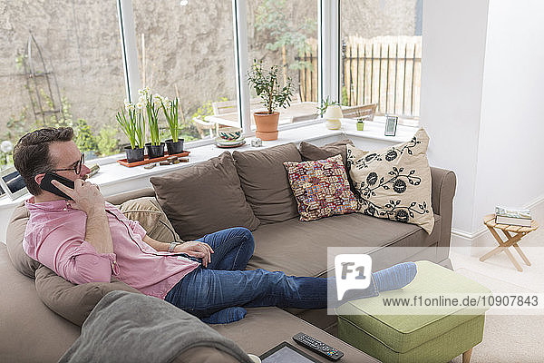 Mature man sitting on couch talking on the phone
