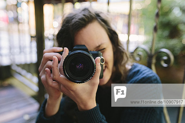 Young woman on balcony using vintage camera