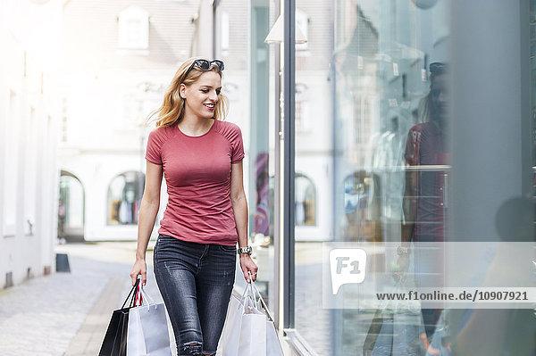 Young woman carrying shopping bags looking in shop window