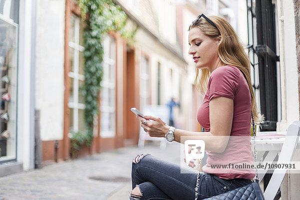 Junge Frau sitzt auf dem Bürgersteig und schaut auf ihr Smartphone.