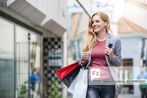 Lächelnde Frau auf der Straße mit Einkaufstaschen