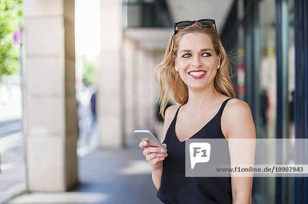Portrait of smiling young woman with smartphone watching something