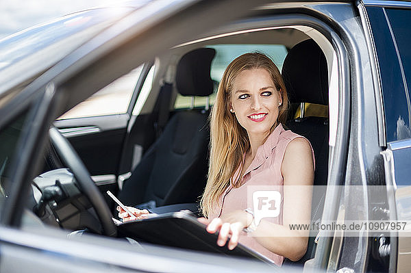 Portrait of smiling young businesswoman with cell phone and file sitting in her car