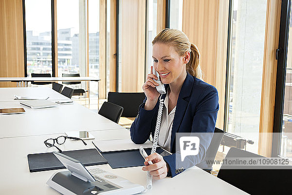 Smiling businesswoman at office desk on the phone