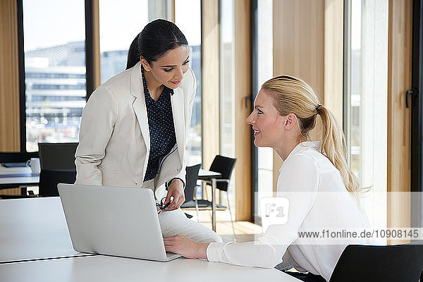 Two businesswomen in office working together on laptop