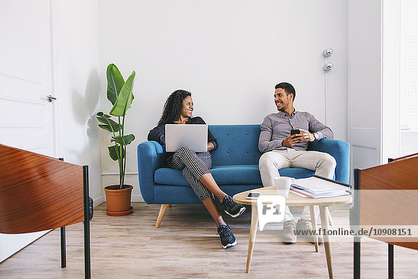Junge Geschäftsleute arbeiten entspannt auf der Couch