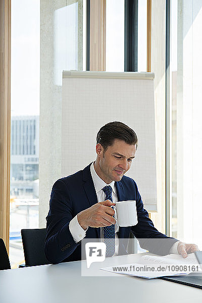 Businessman at office desk reading document