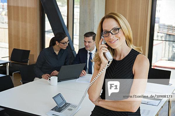 Porträt der lächelnden Geschäftsfrau am Telefon mit Kollegen im Hintergrund