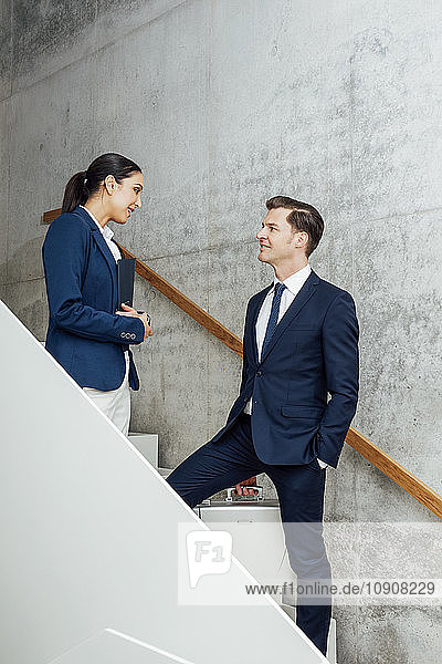 Two business colleagues talking in staircase