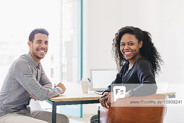 Young businessman and woman working together in office  using laptop