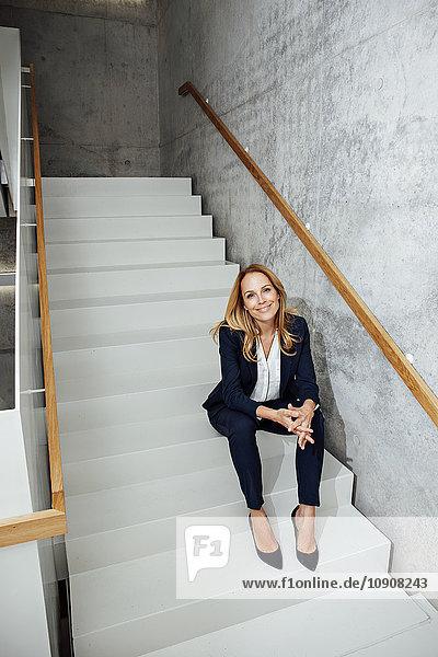 Porträt einer lächelnden Geschäftsfrau auf der Treppe sitzend