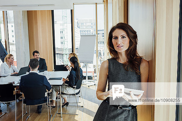 Businesswoman in office with meeting in background